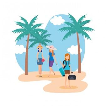 Toeristenmeisjes met koffers op het strand