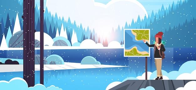 Toeristische wandelaar met rugzak op zoek reiskaart vrouw reiziger planning route wandelconcept zonsopgang winter sneeuwval landschap natuur rivier bos bergen