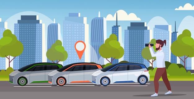 Toevallige mens die door verrekijkers zoeken die auto met plaatsspeld zoeken het concept van het autodelen van de autoharing van de autoharing de dienst moderne cityscape achtergrond horizontale volledige lengte als achtergrond