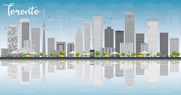 Toronto skyline met grijze gebouwen, blauwe lucht en reflectie.