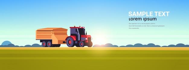 Tractor met aanhangwagen zware machines die in gebied werken slimme landbouw moderne technologieorganisatie van het oogsten van het concept van het zonsonderganglandschap vlakke horizontale exemplaarruimte als achtergrond