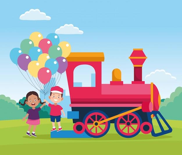 Train en gelukkige kinderen met kleurrijke ballonnen in het veld