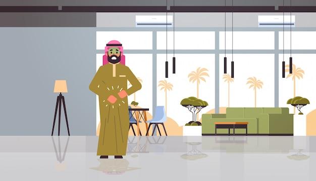 Triest arabische man met bleek gezicht braaksel misselijkheid maagpijn voedsel of alcohol vergiftiging spijsvertering probleem concept arabisch karakter ziek modern restaurant interieur plat volledige lengte horizontaal