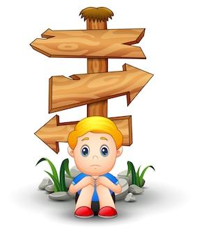 Trieste jongen cartoon zitten onder lege houten pijl teken