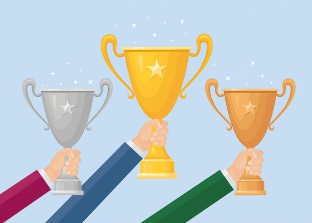 Trofee beker in de hand. goud, zilver, bronzen beker op achtergrond. prijzen voor winnaar, kampioen. concept van overwinning, onderscheiding, kampioenschap, leiderschap, prestatie.