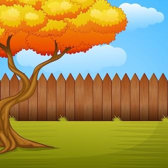 Tuinachtergrond met de herfstboom en houten omheining