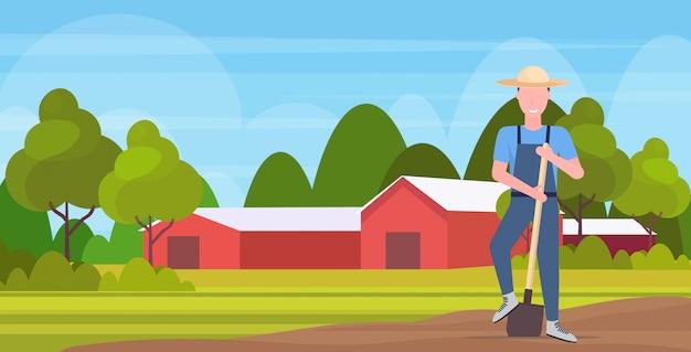 Tuinman die schop glimlachende landgenoot houden die aan gebieds landbouw het planten het oogsten het tuinieren eco van het het landbouwgrondplatteland van het landbouwlandschap volledige horizontale lengte werken