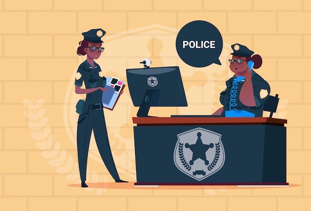 Twee afrikaanse amerikaanse politievrouwen die aan computer werken die eenvormige vrouwelijke wachten op blauwe bakstenenachtergrond dragen
