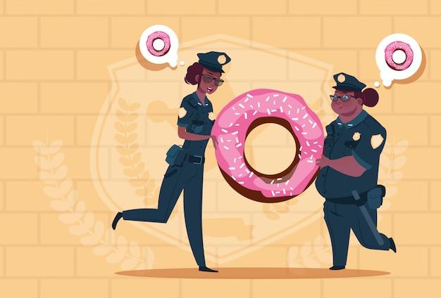 Twee afrikaanse amerikaanse politievrouwen die doughnut houden die eenvormige vrouwelijke wachten op blauwe bakstenenachtergrond dragen