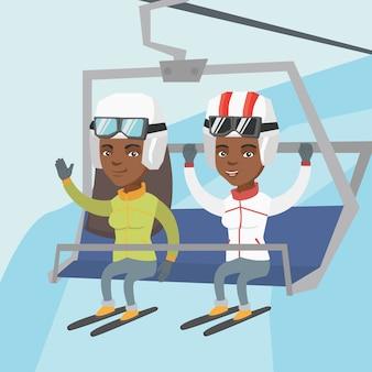 Twee afro-amerikaanse skiërs met behulp van kabelbaan.