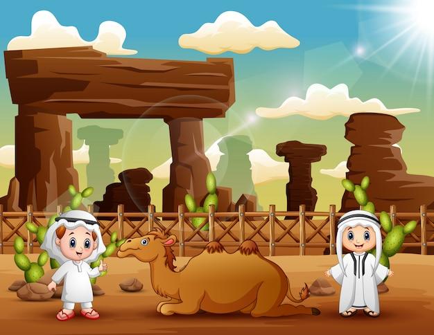 Twee arabische jongens met kamelen in de woestijn