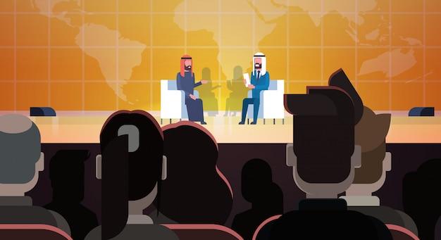Twee arabische zakenlieden of politici op conferentie of debat meeting interview talking sit over world map voor groot publiek