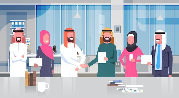 Twee arabische zakenmanleiders handshake over team van moslim bedrijfsmensen in modern bureauvennootschap en overeenkomstconcept