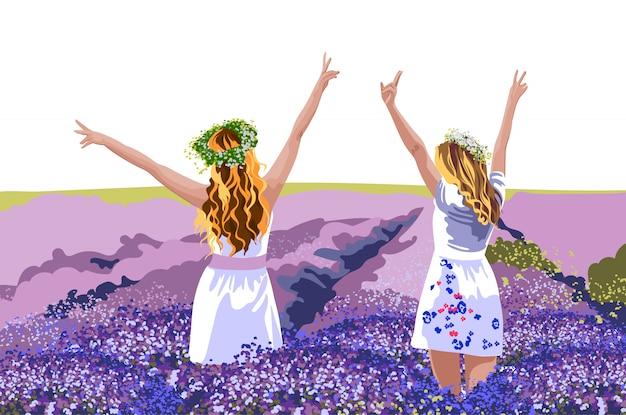 Twee blonde vrouwen in witte jurken met bloemenkronen op het hoofd staan in lavendelveld met hun handen omhoog