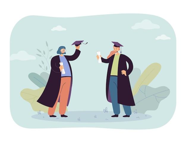 Twee cartoon vrouwelijke afgestudeerden in toga's en hoeden. vlakke afbeelding