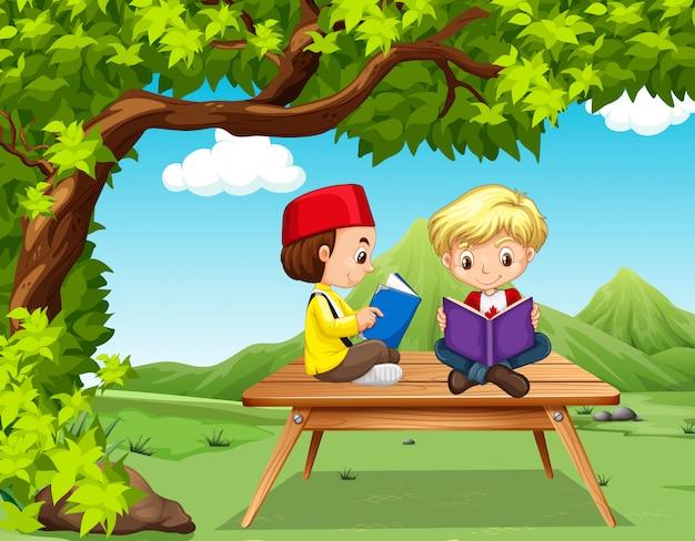 Twee jongens die boeken in het park lezen