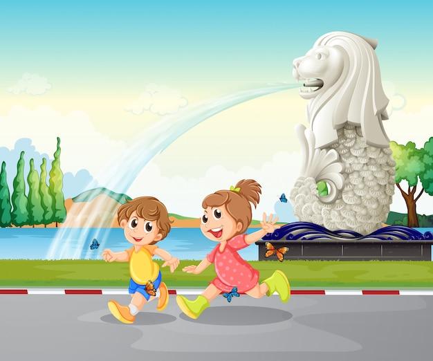 Twee kinderen spelen in de buurt van het standbeeld van merlion