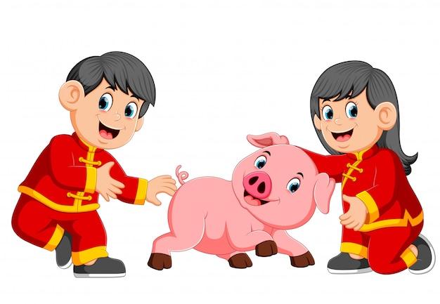 Twee kinderen spelen met een klein varken in chinees nieuwjaar