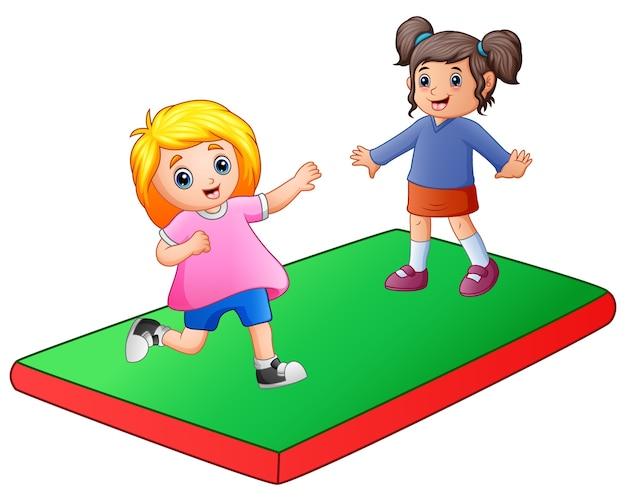 Twee klein meisje spelen op de mat