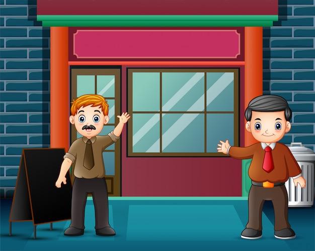 Twee man zwaaien hand vooraan een winkel