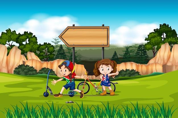 Twee meisjes met fietsen en scooters
