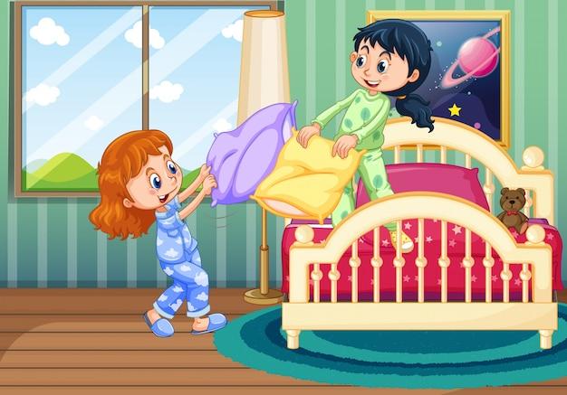 Twee meisjes spelen kussengevechten in de slaapkamer