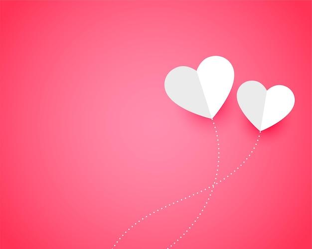 Twee papieren harten op roze met tekstruimte
