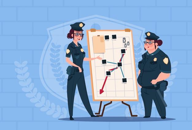Twee politievrouwen die actie op witte raad plannen die eenvormige vrouwelijke wachten op blauwe bakstenenachtergrond dragen