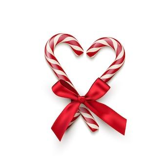 Twee rode gestreepte zuurstokken in hartvorm met rode strik op witte achtergrond.