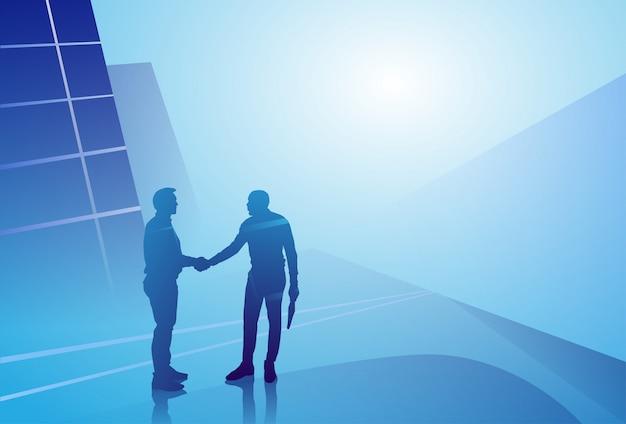Twee silhouetzakenman handschok, de overeenkomstconcept van de bedrijfsmensenhanddruk