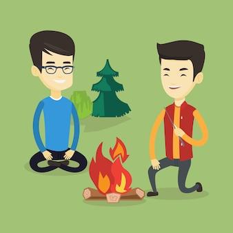 Twee vrienden zitten rond vreugdevuur op de camping.