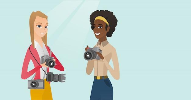 Twee vrouwelijke multiraciale fotografen die foto's nemen