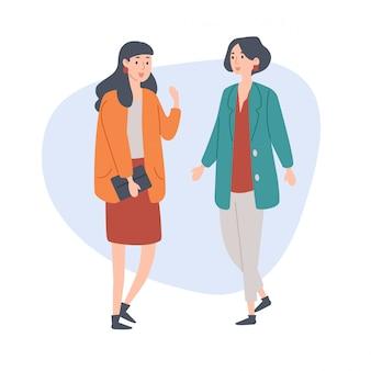 Twee vrouwelijke vrienden praten met elkaar.