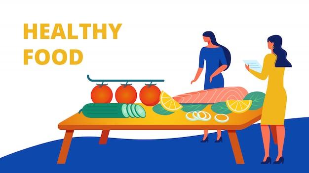 Twee vrouwen in jurken in de buurt van tabel met gezonde maaltijd