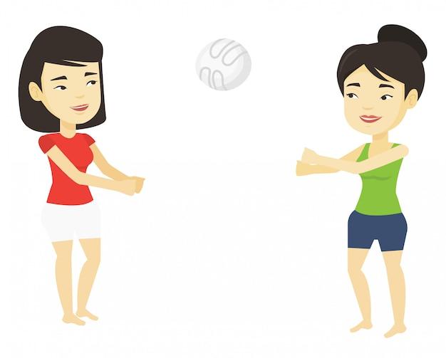 Twee vrouwen spelen beachvolleybal.