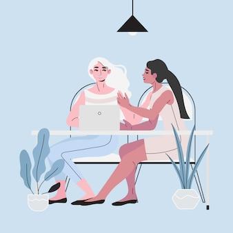 Twee zakelijke vrouw zitten aan een tafel met een laptop.
