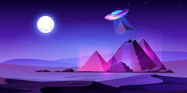 Ufo steelt egypte piramides top in nacht woestijn, buitenaardse schotel trek stuk van egyptische farao tombe in lichtstraal.