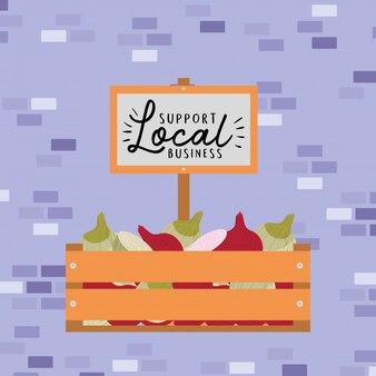Uien in houten kist en ondersteunen lokale bedrijven op banner
