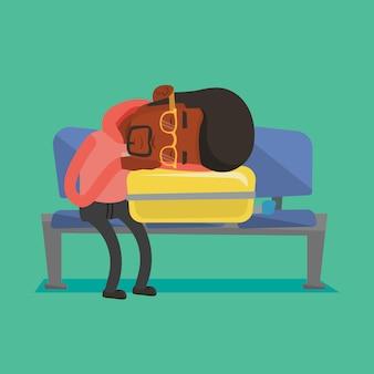 Uitgeputte man slapen op koffer op luchthaven.