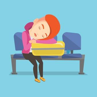 Uitgeputte vrouwenslaap op koffer bij luchthaven.
