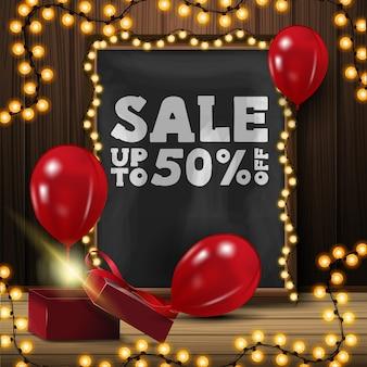 Uitverkoop, tot 50% korting, banner met krijtbord, gele slinger, cadeau en rode ballonnen