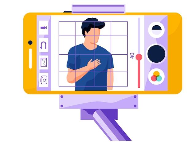 Uitzending vanaf een telefoon die is bevestigd aan een monopod. de man staat met de hand op het hart. fotobewerkings-app voor smartphones. foto van een knappe man met filters op het scherm van een telefoon. de jongen poseert om te schieten