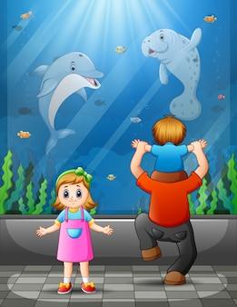 Vader en kinderen kijken naar vissen bij aquariumexcursie