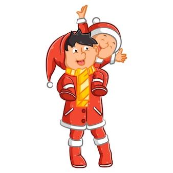 Vader en zijn zoon die het rode kostuum gebruiken om kerstmis te vieren