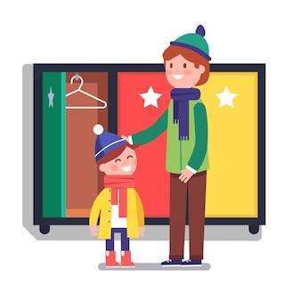 Vader helpen zijn jongen zoon kind om aan te kleden