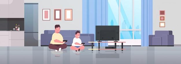 Vader met zoon met joystick gamepad familie die videogames op tv-scherm ongezonde levensstijl