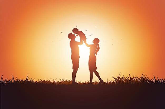 Vader moeder en kinderen silhouet spelen op gras in zonsondergang.