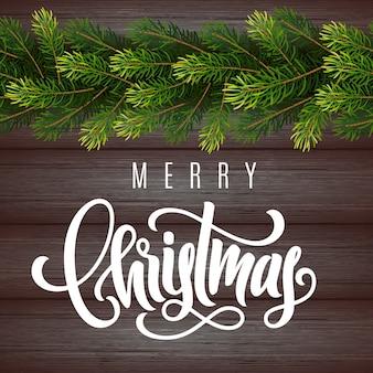 Vakantie geschenkenkaart met hand belettering merry christmas en fir boomtakken op hout achtergrond
