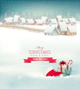Vakantie kerst achtergrond met een dorp, een hoed en een geschenkdoos.