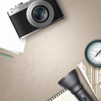 Vector compacte fotocamera met blanco vel papier, kladblok, potlood, kompas, kaart, zaklamp en plaats voor copyspace bovenaanzicht op tafel